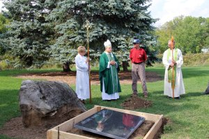 Bishop Michael blesses the natural burial ground at St. John's Jordan ╨ believed to be one of only five in Canada ╨ as Server Sue Bailey, Diocesan Cemetery Consultant Brian Culp and Rector Kevin Block observe.Photo: Brenda Lane