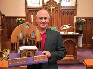 John Reaume holds the model of the sanctuary of St. George's Georgetown, which he carved from an old wooden pew. Photo: Rob Park